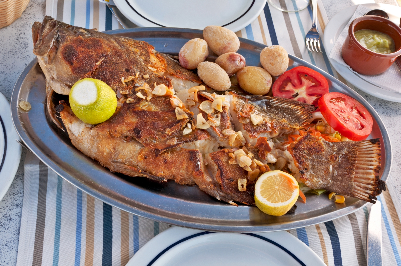 'Typical Canarian Roasted sea fish on plate with tomatoes, potatoes, lemon and spices' - Lanzarote